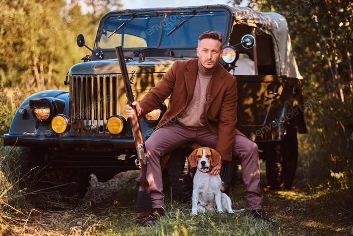 Hunter in elegant clothes together with his beagle dog next to a retro military car in the forest.