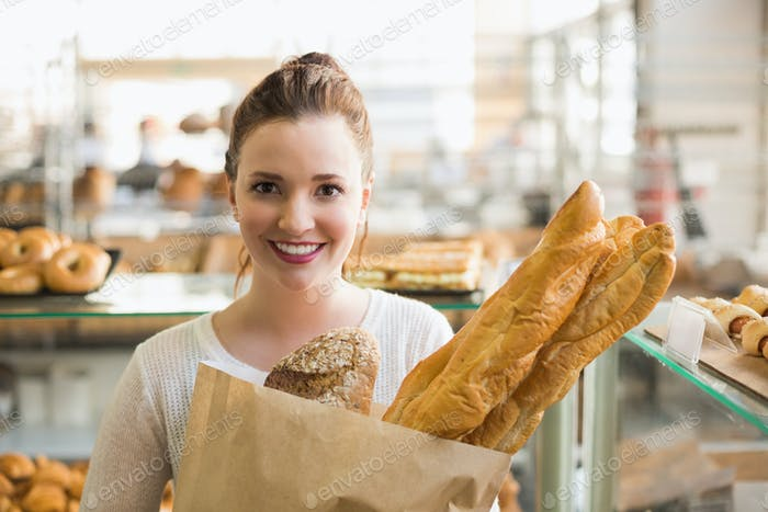Pretty brunette with bag of bread at the bakery