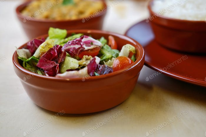 Closeup photo of vegetable salat in bowl with traditional indian dishes at background