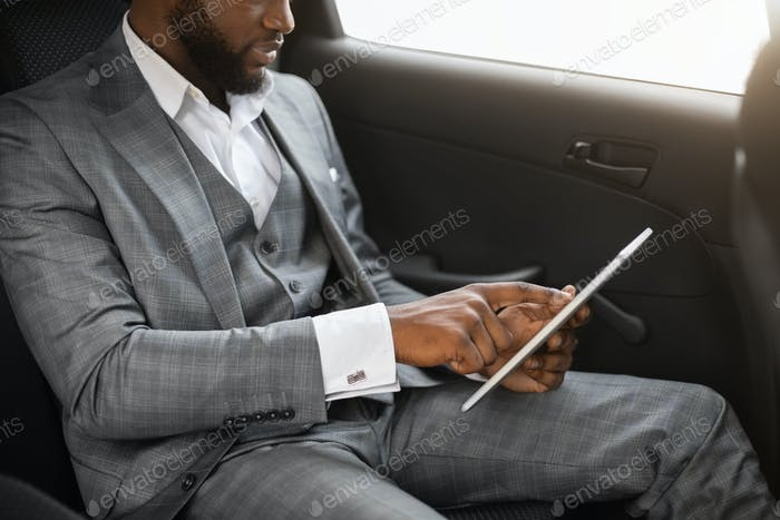 Unrecognizable african businessman using digital tablet in car