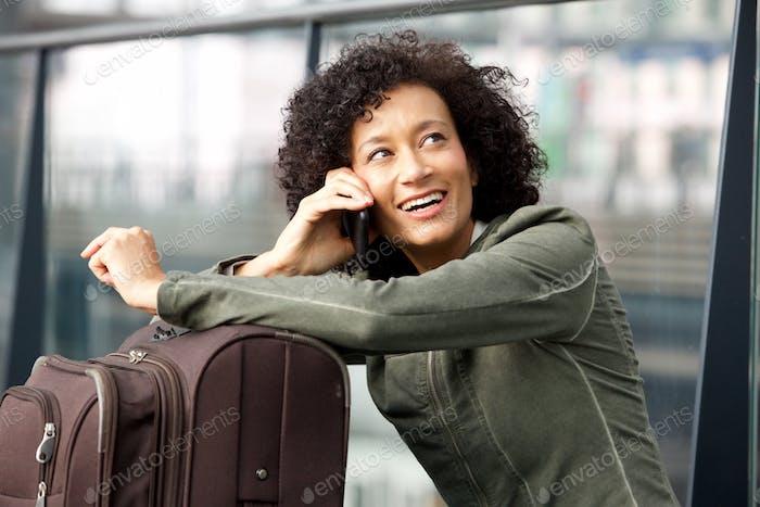 Close up happy female traveler talking on mobile phone