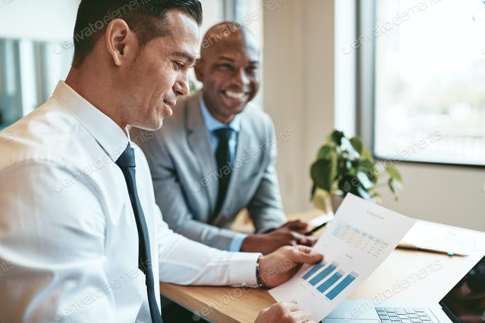 Two smiling diverse businessmen discussing paperwork together in an office
