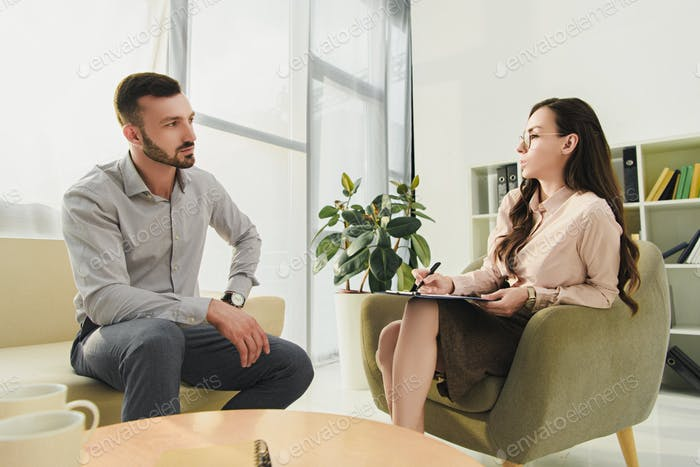 professional psychologist talking with patient in office
