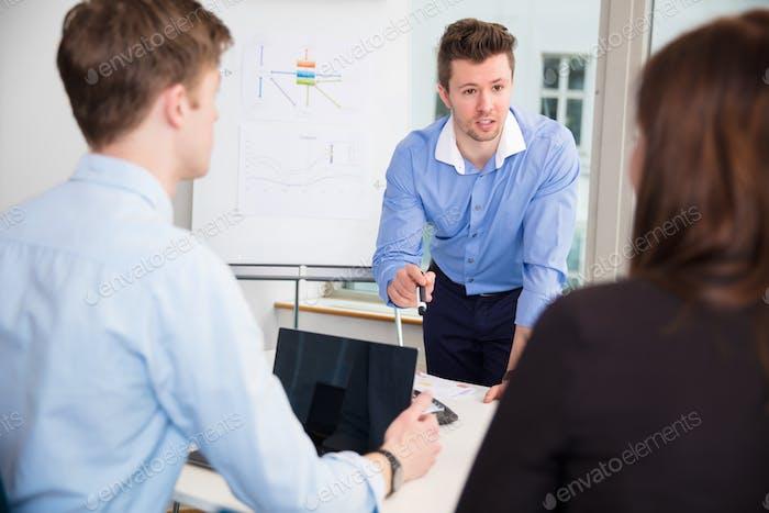 Бизнесмен, обсуждающий с коллегами в офисе