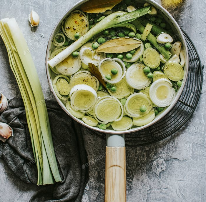 Cooked leeks with peas in a pot