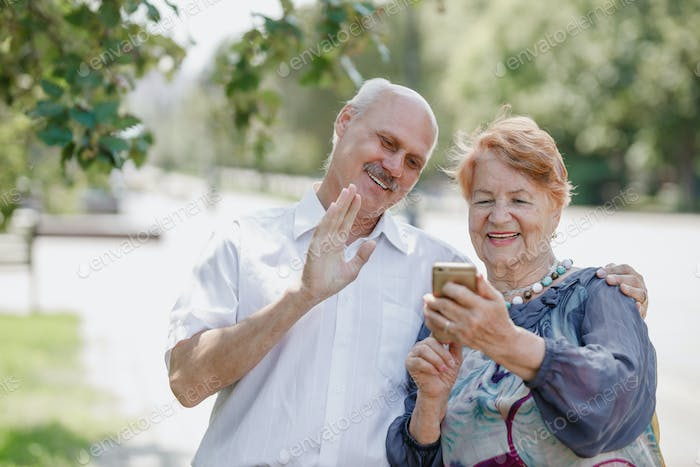 Old man and old woman are using together one phone and smiling while walking in a park on a warm day