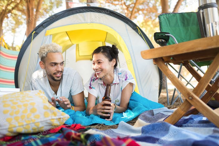 Smiling couple having drink while relaxing tent