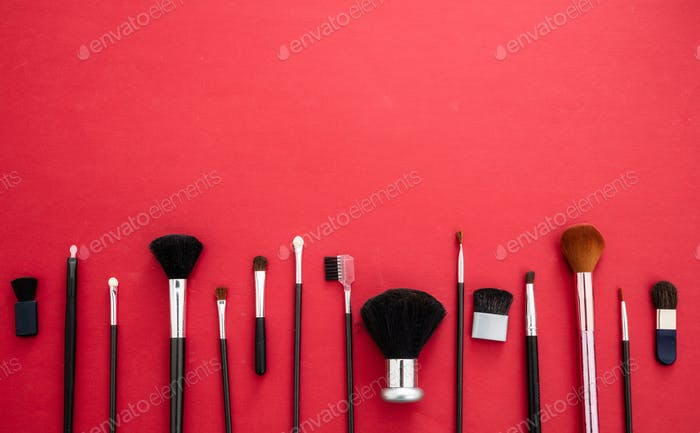 Make-up brushes set against red background, copy space