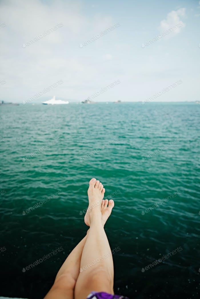 Crop female feet above sea water