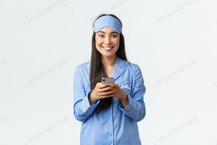 Technology, people and home leisure concept. Smiling cute asian female blogger in pajamas and