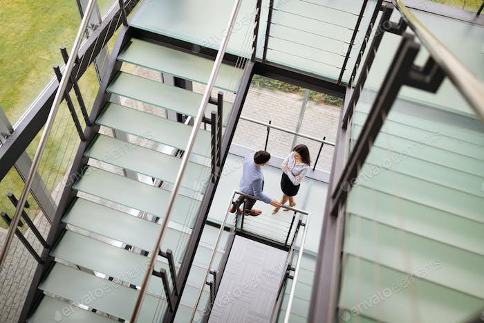 Modern business people walking on stairs in glass hall in office building