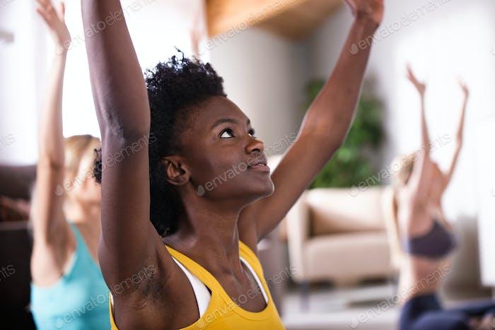 Gruppe von hübschen jungen sportlichen Frauen praktizieren Yoga zu Hause
