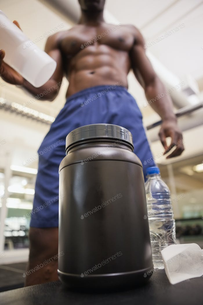 Shirtless body builder scooping up protein powder in gym