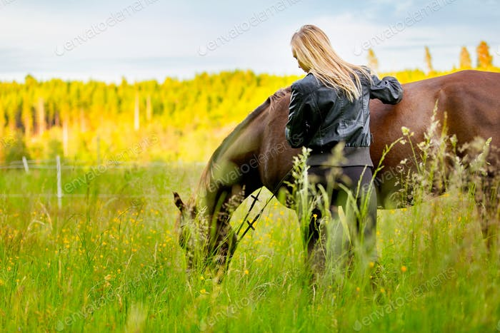 Beautiful woman patting her arabian horse standing in the field