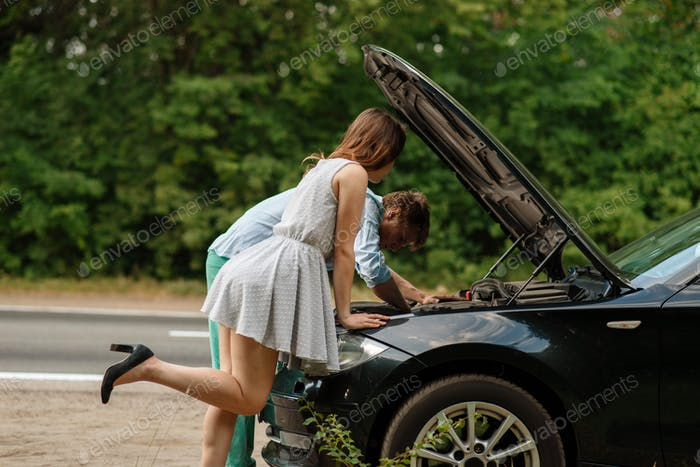 Man and woman repair auto on road, car breakdown