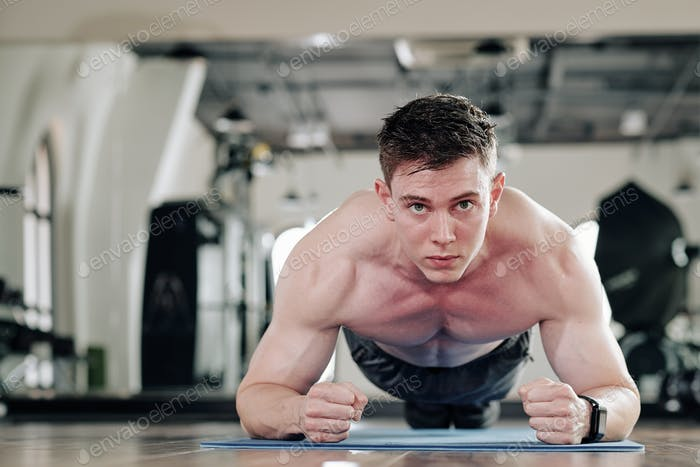 Shirtless man in plank position
