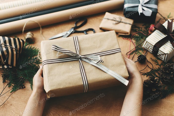 Hands holding stylish christmas gift box in craft paper and scissors, rustic  presents