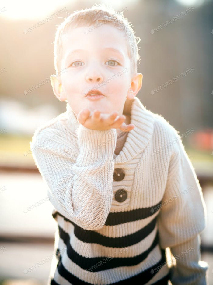 Child blowing kiss, little boy playing outdoor
