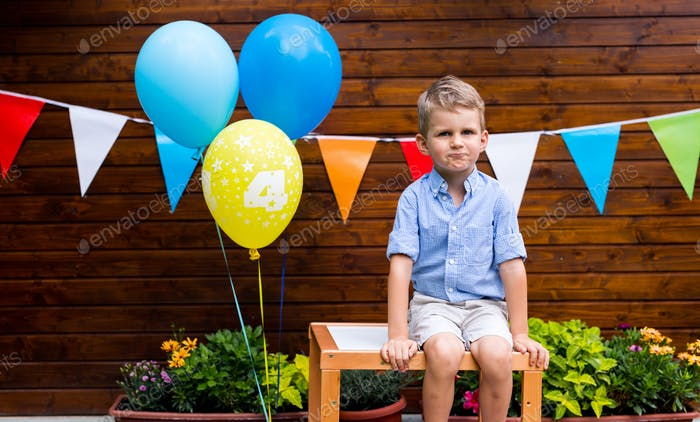 Portrait of young boy sitting on table at birthday party