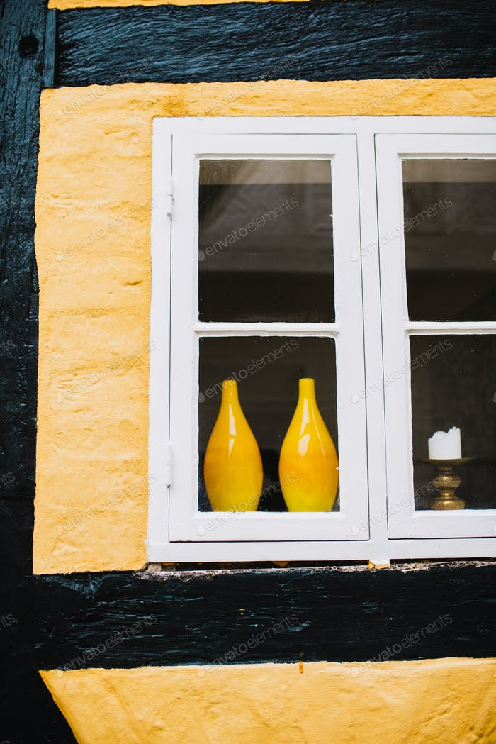 Pair of yellow vases in window