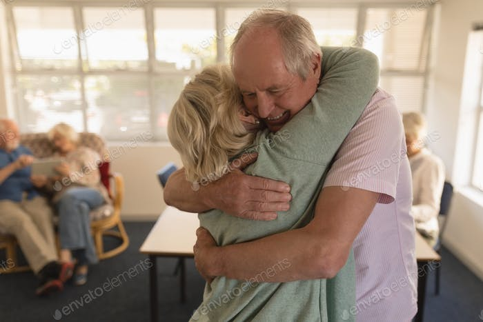 Senior couple embracing each other while senior people are sitting behind  at nursing home