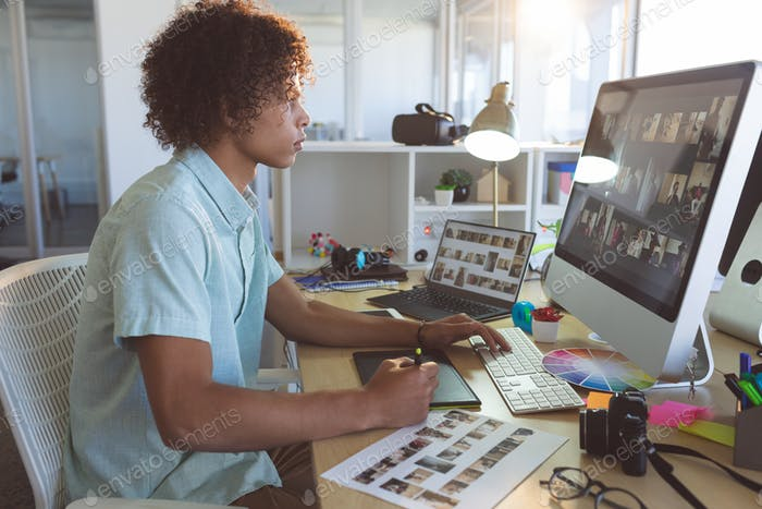 Male graphic designer using graphic tablet at desk in a modern office