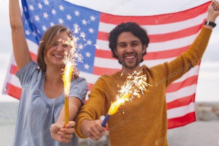 Junges Paar spielen mit Feuer Cracker während halten amerikanische Flagge