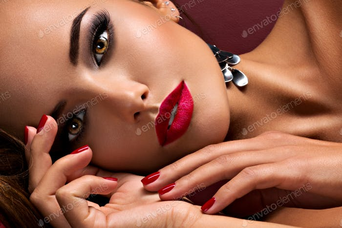 Beautiful  woman with bright eye makeup and  red lips lying on t