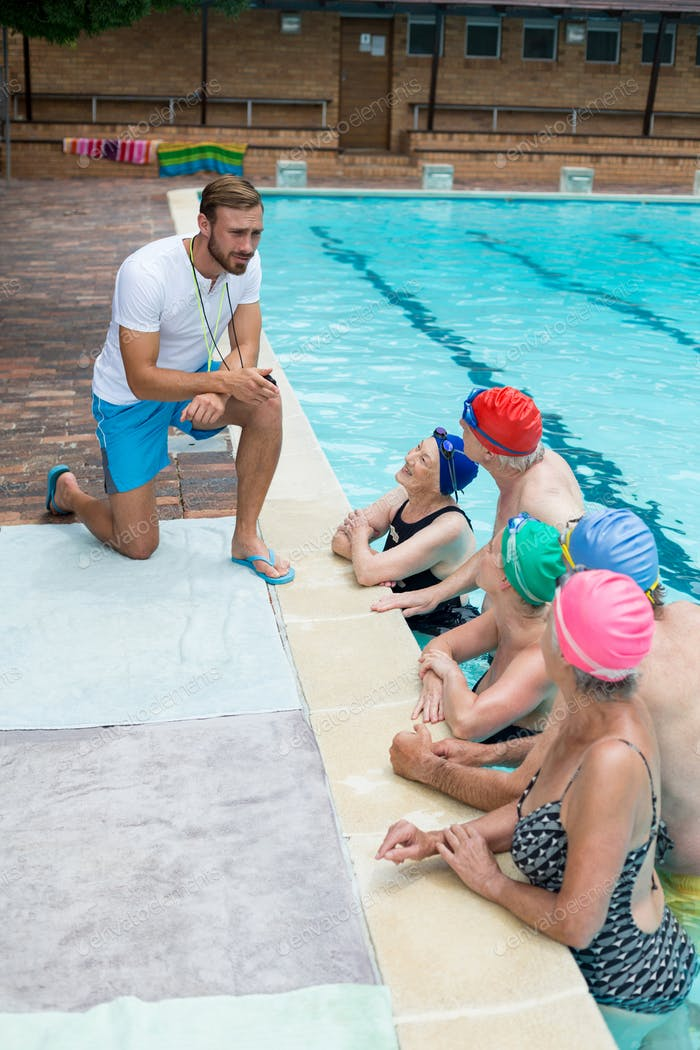 Instructor assisting senior swimmers at poolside