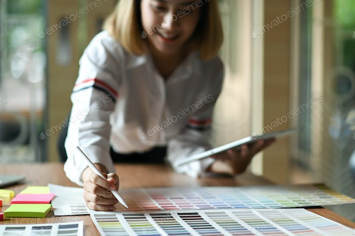 Asian female graphic designer working in office. She uses tablet and point the pen on color chart.