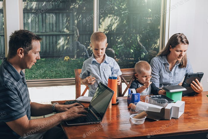 Concept of work from home and home family education. Parents and two sons are sitting at the desk.