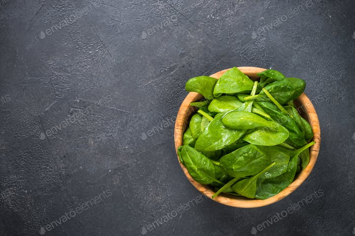 Baby spinach leaves on black background