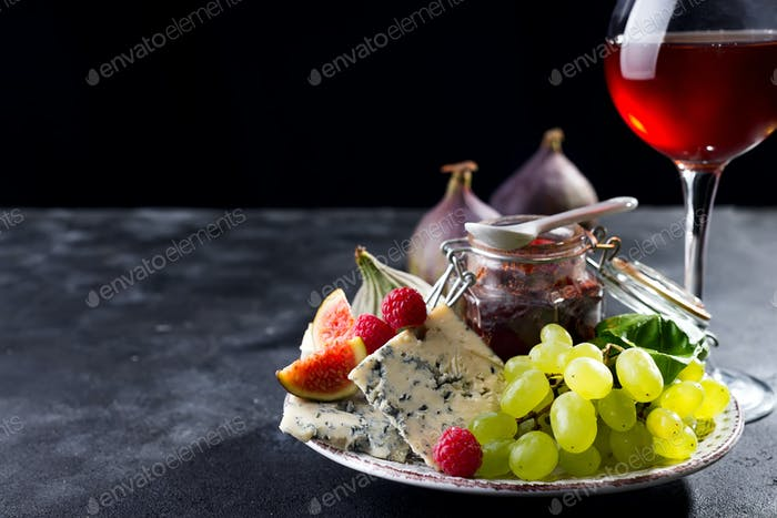 delicacy blue cheeses, fruit and jam in jar with red wine in glass on black slate