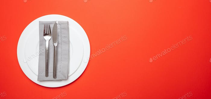 Set of empty white plates and cutlery on red, orange color background, banner