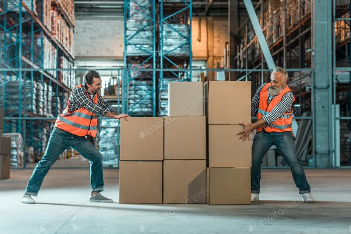 warehouse workers moving boxes while working together in storehouse