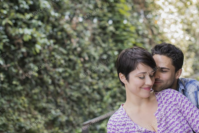 A couple in a city park beside a green wall of foliage embracing.