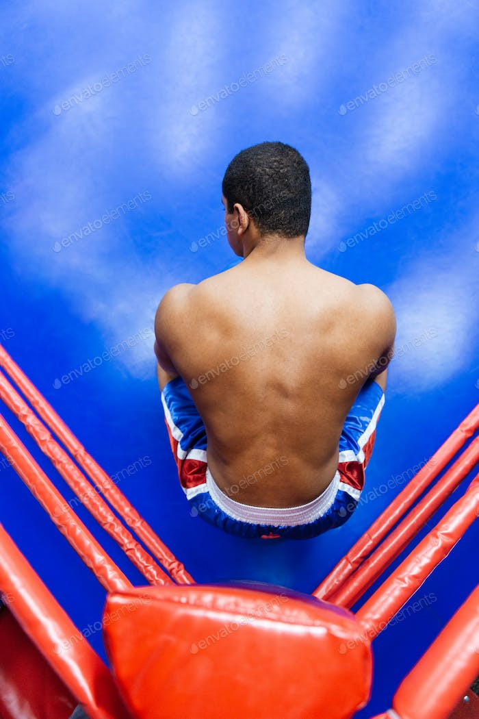 Boxer sitting in the corner of boxing ring
