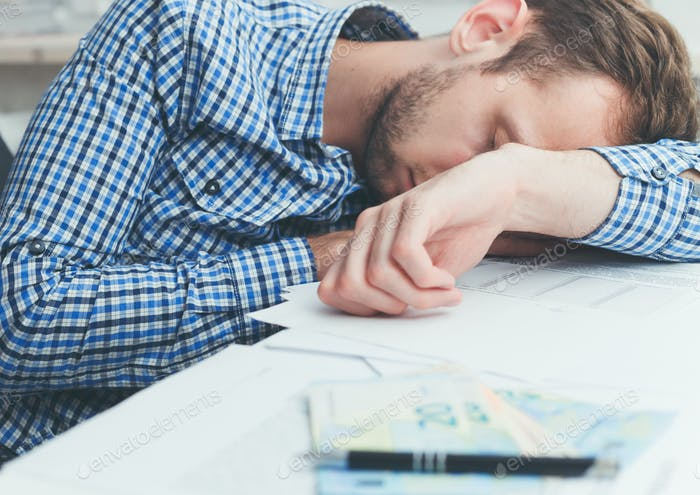 Overworked and tired office worker sleeping over at work on table in office