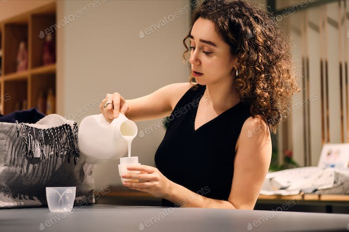 Attractive girl intently using detergent bottle washing clothes in modern self-service laundry
