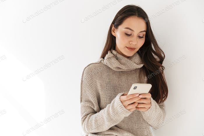 Image of pleased asian woman posing and using smartphone