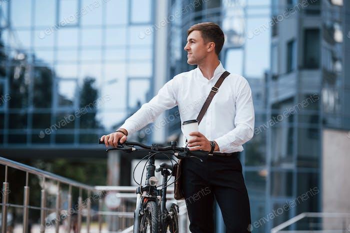 Voller Energie. Geschäftsmann in formeller Kleidung mit schwarzem Fahrrad ist in der Stadt