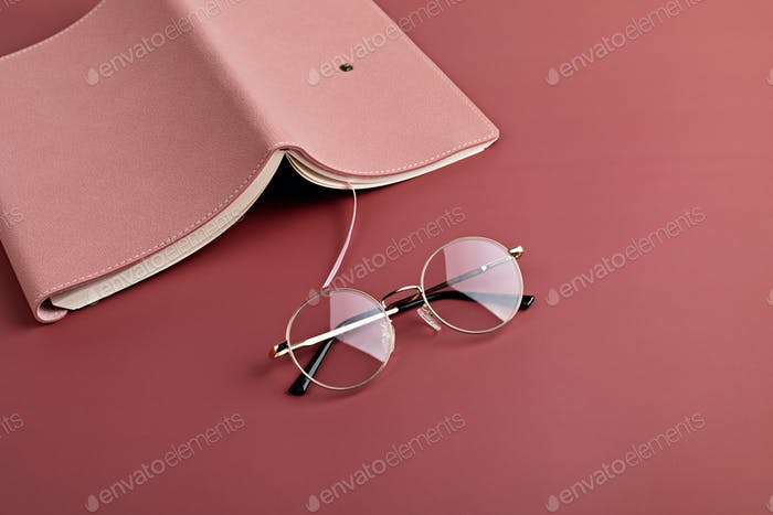 daily planner and reading glasses on pink background