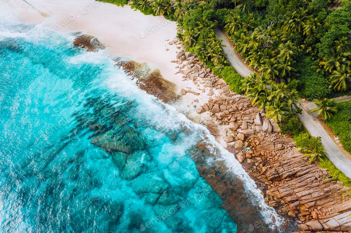 Aerial photo of ocean waves hitting rocky coastline of beautiful paradise dream tropical beach at