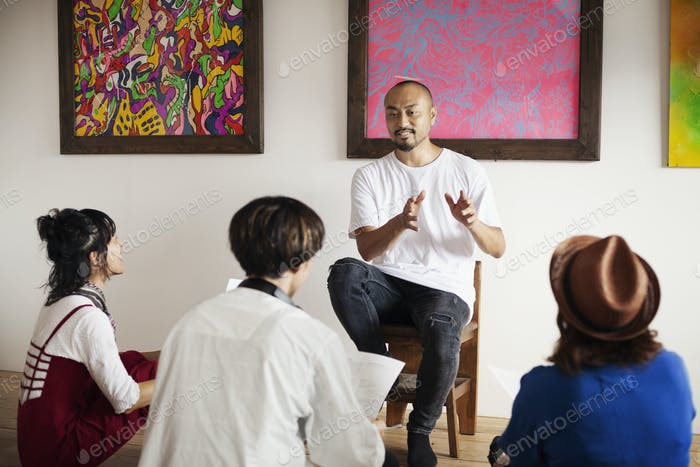 Group of Japanese men and women sitting in art gallery, holding a discussion.