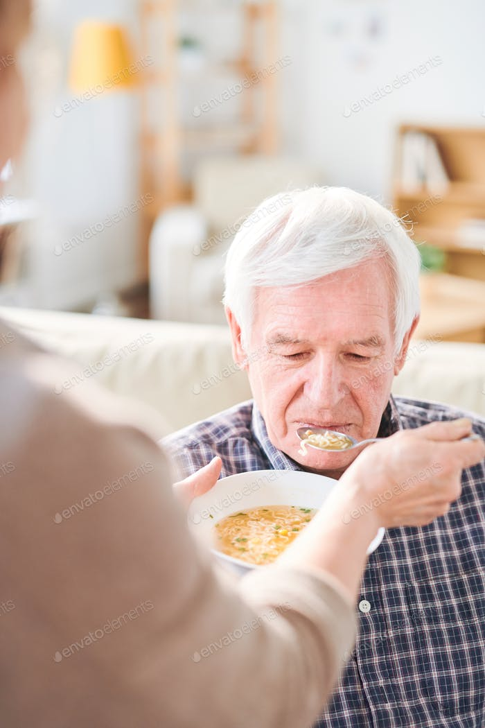 Feeding disable man with soup