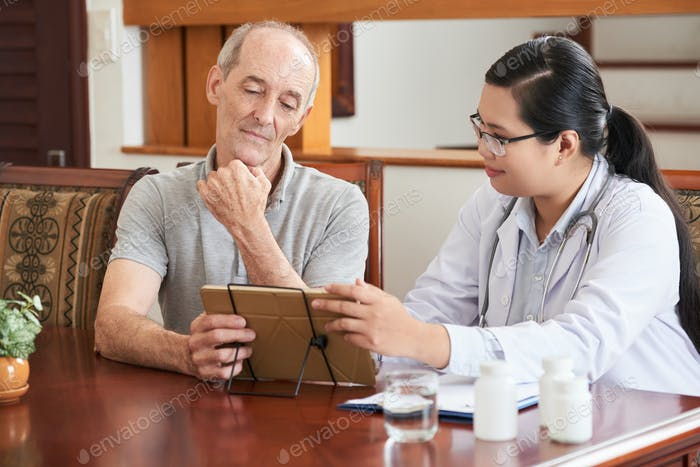 Woman showing tablet to elderly patient