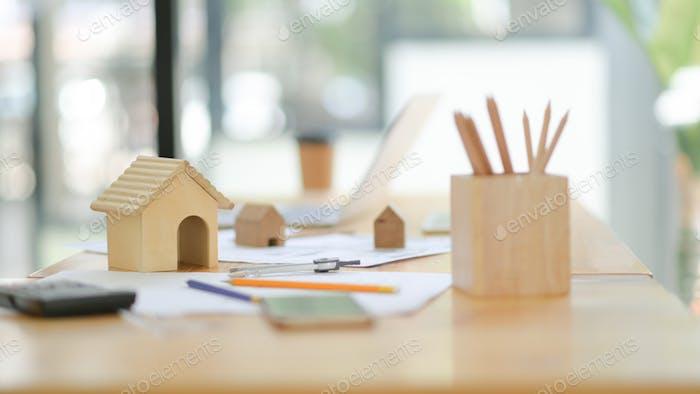 Mockup Haus Zeichenwerkzeuge und Holzmodellhaus auf dem Schreibtisch im Büro.