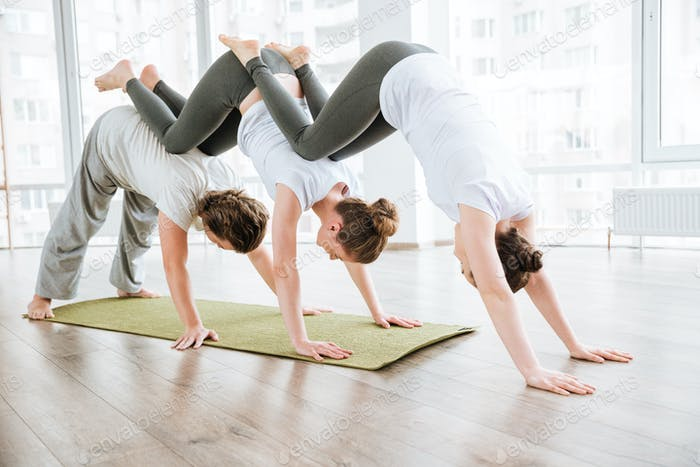 Man and two women practicing acro yoga in group