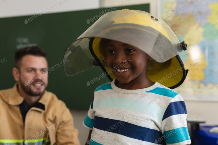 Happy schoolboy wearing fire helmet with smiling firefight behind him in classroom