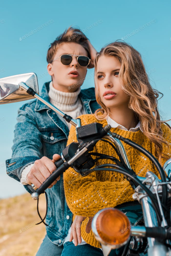 Young Couple Sitting on Motorbike Against Blue Sky